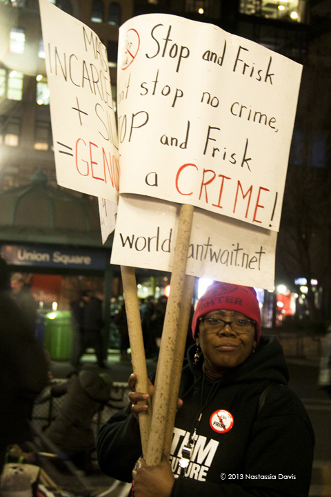 Stephanie Colon, a member of the Stop Mass Incarceration Network, holds up signs at Trayvon Martin Vigil on Tuesday, February 26, 2013.