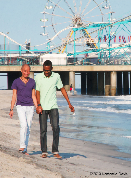 Gay male couple  walking together on the beach by Atlantic City's Steel Pier.