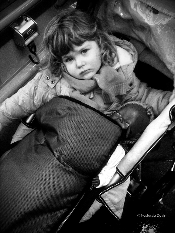 "Child with baby doll on tram in Switzerland. ""It's her favorite one."" said her mother, as I took the photo."